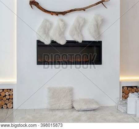 Fireplace With Christmas Stockings And Gifts In Interior Of Room. White Fireplace Is Decorated With