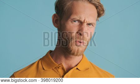 Young Bearded Man Unpleasantly Looking In Camera Over Colorful Background. Disgusted Expression