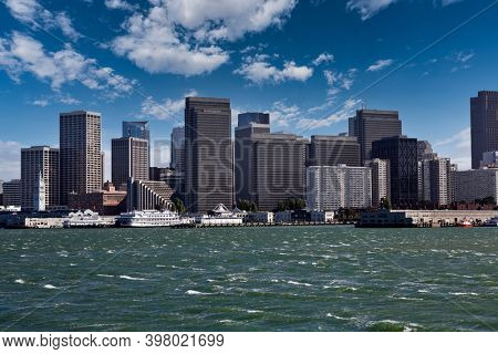 View of wind blown water and downtown towers with partly cloudy sky in San Francisco Bay.
