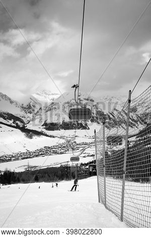 Chairlift, Snowy Ski Slope With Snowboarders And Skiers In High Mountains And Cloudy Sunlit Sky At W
