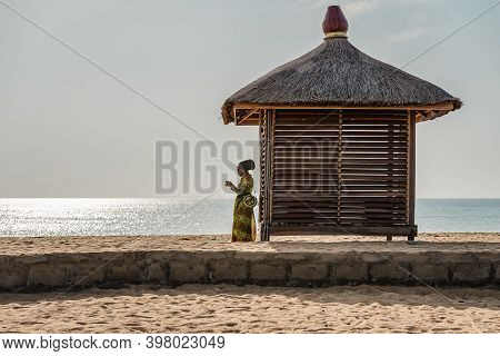 African Woman Standing Next To A Bungalow Alone Wearing African Clothes On The Coast Of Africa In Ke