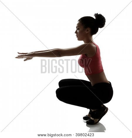 sport young woman athlete doing squatting exercise, active fitness girl silhouette studio shot over white background