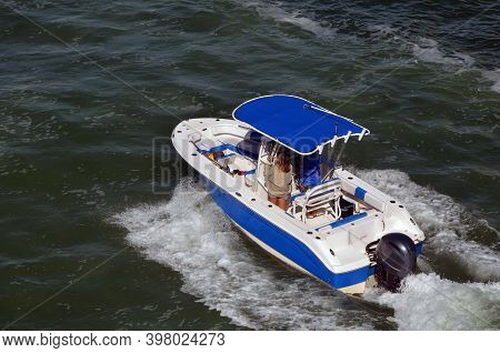 Blue And White Sport Fishing Boat Powered By A Single Outboard Engine Cruising On The Florida Intra-