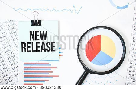Green Card On The White Notepad And Magnifier On The Financial Documentation. Text New Release. Busi