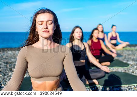 Group Of Five Women Practicing Yoga Assans In Morning Beach . Only Girls Session