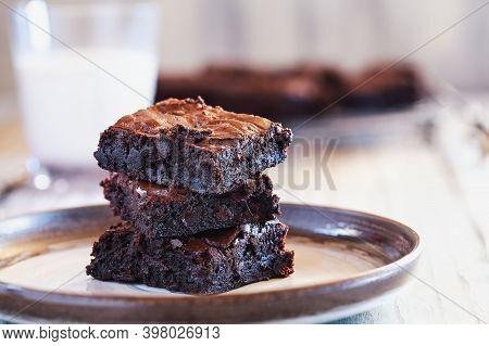 Fresh Made Homemade Fudgy Brownies Stacked On A Saucer Over A White Rustic Wooden Table. Extreme Sha