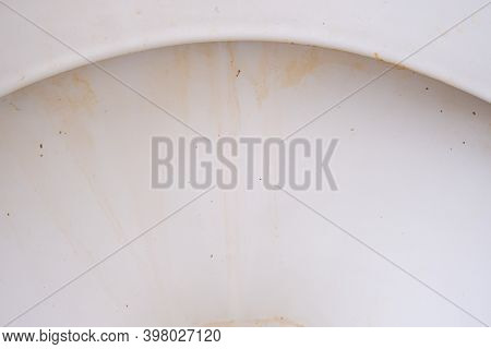 Dirty Unhygienic Toilet Bowl With Limescale Stain At Public Restroom Close Up.