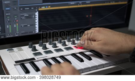 Male Hands Recording Music, Playing Electronic Keyboard, Midi Keys On The Table. Closeup Of Male Han