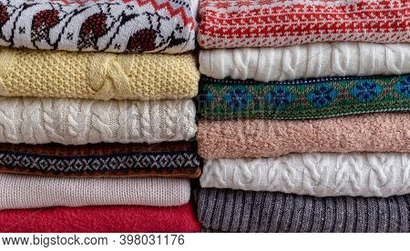 A Lot Of Different Sweaters And Pullovers Folded In Two Piles On The Table