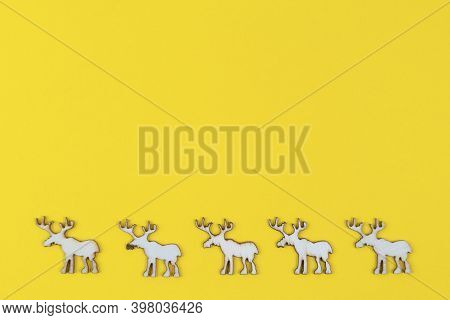 A Row Of Small Wooden Reindeer Figures On A Yellow Background