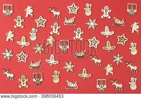 A Texture Formed By Small Wooden Christmas Icons On A Red Background