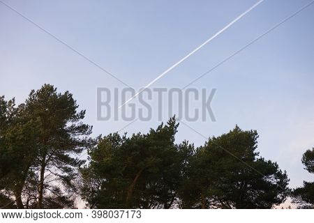 Large Airliner Leaves Vapour Contrails Behind, Due To Its Engine Exhaust Fumes In The Atmosphere, As