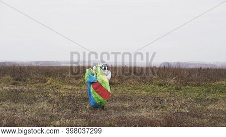 Parachutist Walking With A Bright Chute In His Hands After Landing On A Field. Action. Male Jumper I