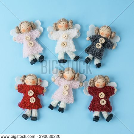 Some Small Handcrafted Dolls On A Blue Background
