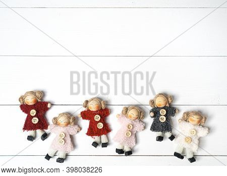 Some Small Handcrafted Dolls On A Wooden White Background