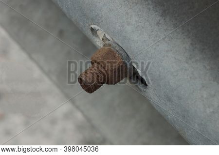 One Old Brown Rusty Bolt With A Twisted Nut On A Gray Metal Wall