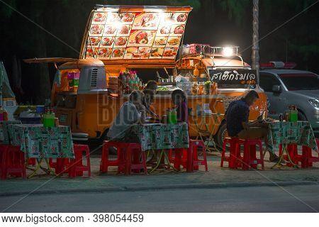 Cha Am, Thailand - Dec 10, 2018: Thai Women Help European Tourist To Choose National Food In Night S