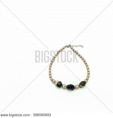 Women's Bijouterie. Necklace Made Of Pale Pink And Black And White Beads. Metal Clasp. Isolated On W