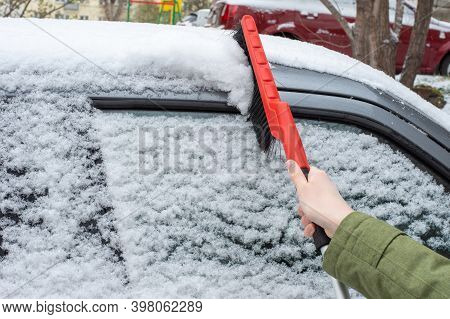 Winter Problems Of Car Drivers. Close-up Of A Female Hand Holding A Red Brush. A Driver Removes Snow