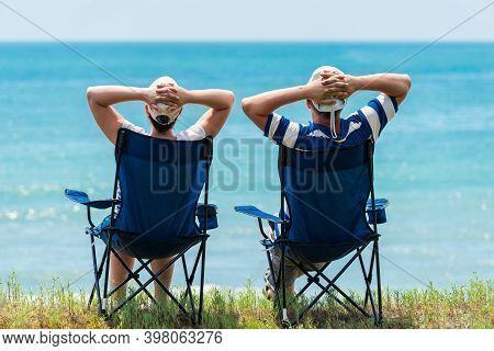 Man And Woman Relax And Unwind In Camping Chairs On The Seashore