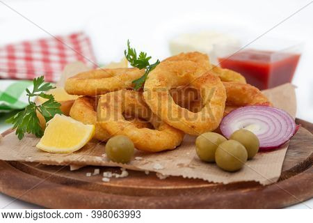 Deep Fried Squid Or Fish Rings Appetizer. Breaded Squid Or Fish Rings With Lemon,  Ketchup And Mayon