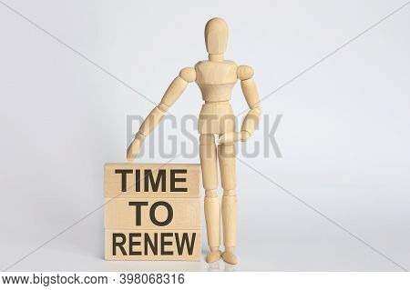 Wooden Man Shows With A Hand Text Time To Renew Concept On The Wooden Block