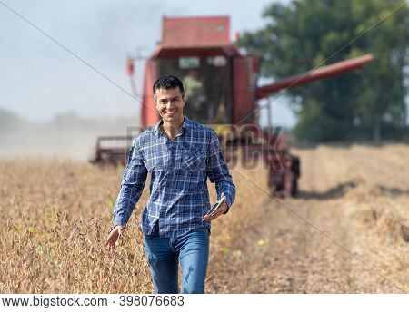 Handsome Farmer Standing In Soybean Field And Holding Tablet While Combine Harvester Working In Back