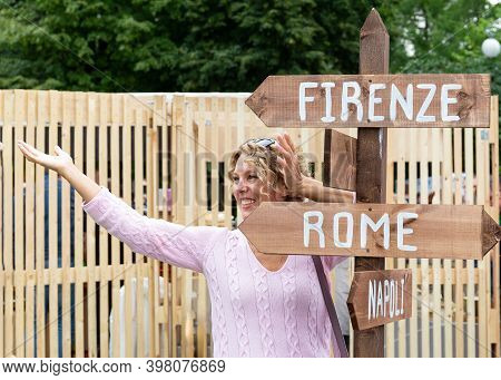 Moscow, Russia, July 13, 2019: A Smiling Blonde Woman Stands At A Pillar With Directions Indicating