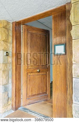 Half Opened Front Wooden Door And Door Sign At Yellow And Gray Decorative Uneven Stone Bricks Wall
