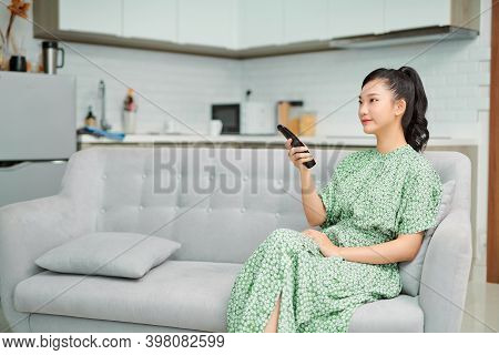 Happy Pretty Girl With Remote Control Watching Tv
