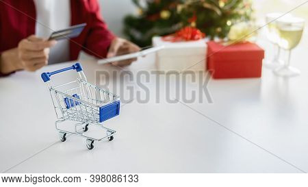 Online Shopping Concept. Shopping Cart On White Table With Asian Woman Holding Smartphone And Using