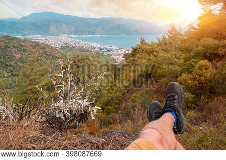 Man Is Resting And Enjoying Resting The Sunset After Mountain Trekking. First-person Shooting. Feet