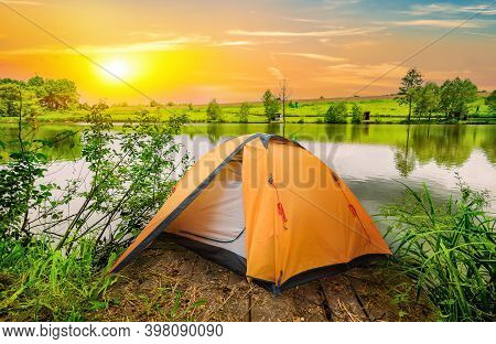 Tent And Calm River In The Morning