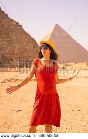 A Young Girl In A Red Dress At The Pyramid Of Cheops The Largest Pyramid. The Pyramids Of Giza The O