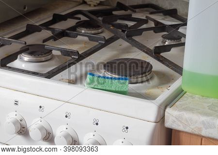 Cleaning A Dirty Stove In The Kitchen With A Sponge With Stove Cleaning.