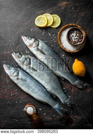 Raw Sea Bass Fish With Sliced Lemon And . On Dark Rustic Background