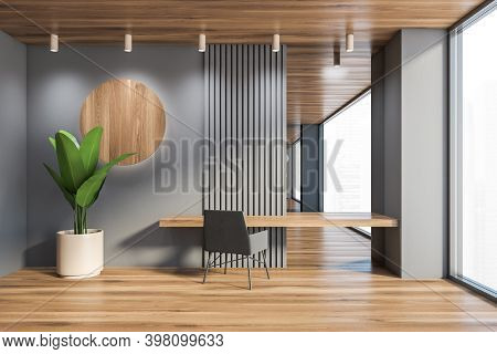 Interior Of Minimalistic Home Office With Gray Walls, Wooden Floor And Table With Gray Armchair. 3d