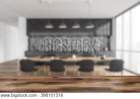 Wooden Desk Foreground, Blurred Grey And Wooden Minimalist Kitchen, Dining Table With Chairs On Back