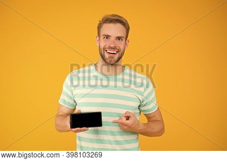 Best Phone Available For You. Happy Guy Pointing At Smartphone Yellow Background. Pointing For Adver
