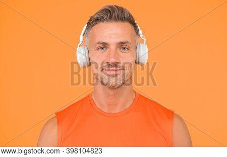 Wireless Is Modern. Clean Sound. Modern Technology. Mature Man Listen Music Wireless Gadget Yellow B