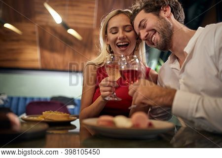 A young couple in love toasting at Valentine's day celebration in restaurant in a relaxed atmosphere. Together, Valentine's day, celebration