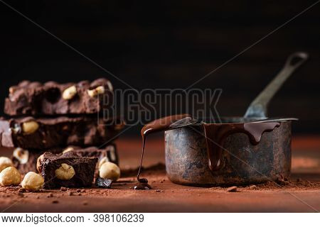 In The Foreground Some Stacked Pieces Of Dark Chocolate With Hazelnuts. Apart From The Copper Saucep