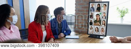 Group Of Men And Women Sit At Table Wearing Protective Face Masks And Stare At Conference Computer S