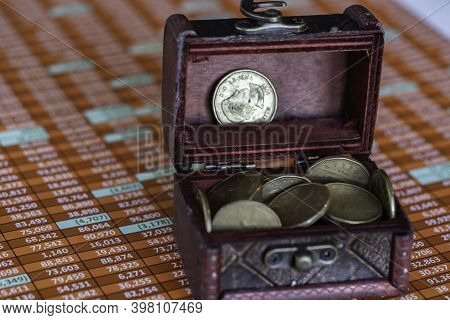 Spreadsheet And Treasure Chest Full Of Canadian Dollar Coins