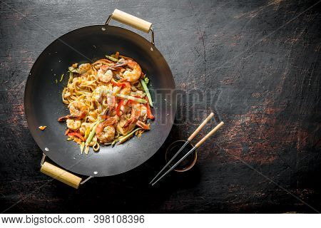 Freshly Cooked Asian Udon Noodles With Vegetables And Shrimp. On Dark Rustic Background