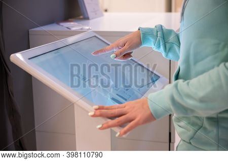 Faceless Woman Touching The Screen Of A Self-service Device In A Store. Device Store Navigator. Self
