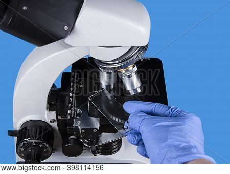 Light Microscope For Observation Of Biopsy, Anatomy Or Histology On Blue Background. Hand In Gloves