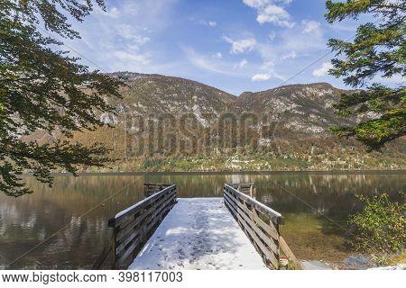 Snow-covered Wooden Pier On Lake Bohinj In Slovenia