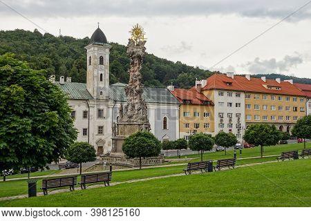 Kremnica, Slovakia - July 3, 2020: Morovy Stlp Sv. Trojice Memorial And The Kostol Svateho Frantiska