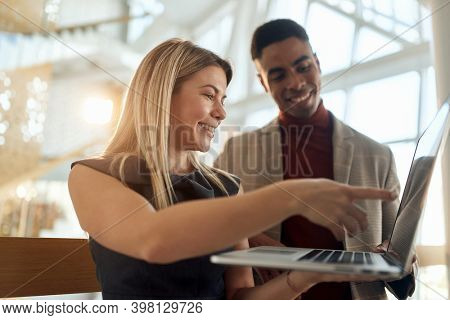 Female employee explaining a job task to a colleague at company's hallway in a pleasant atmosphere. People, job, company, business concept.